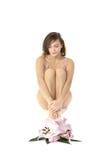 Una mujer joven y atractiva que se sienta con las flores Imágenes de archivo libres de regalías