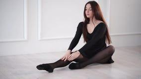 Una mujer joven y bonita se inclina sobre el cuerpo a sus piernas, ella amasa metrajes