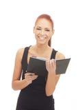 Una mujer joven y feliz que sostiene un cuaderno negro Fotos de archivo libres de regalías