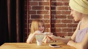 Una mujer joven y una niña comer el yogur en el desayuno almacen de video