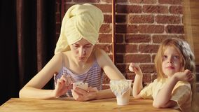 Una mujer joven y una niña comer el yogur en el desayuno metrajes