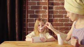 Una mujer joven y una niña comer el yogur en el desayuno almacen de metraje de vídeo