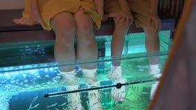 Una mujer joven y su pequeño hijo que visitan un balneario de los pescados Peladura cosm?tica de los pescados del procedimiento almacen de metraje de vídeo