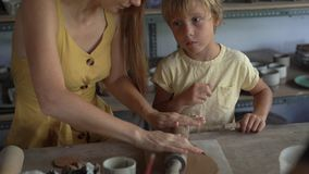 Una mujer joven y su poco hijo en una clase principal de la cerámica almacen de video