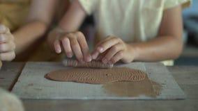 Una mujer joven y su poco hijo en una clase principal de la cerámica metrajes