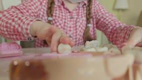 Una mujer joven y un molde de la muchacha sus dientes del plasticine, insertan sus dientes en un mandíbula del juguete, juegan a  almacen de metraje de vídeo