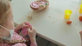 Una mujer joven y un molde de la muchacha sus dientes del plasticine, insertan sus dientes en un mandíbula del juguete, juegan a  metrajes