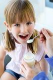 Una mujer joven y una niña que comen el yogur en la cocina Imagen de archivo