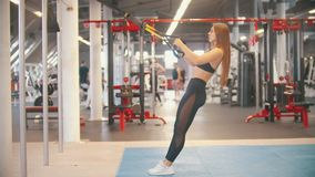 Una mujer juguetona en ropa de los deportes que entrena en el gimnasio - inclinándose reteniendo las manijas almacen de video