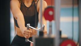 Una mujer juguetona en ropa de los deportes que entrena en el gimnasio - tirando de las manijas conectadas para cargar pedazos almacen de metraje de vídeo