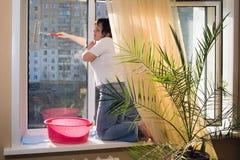 Una mujer lava una ventana fotos de archivo