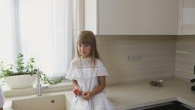 Una mujer lava verduras antes de comer y su hija linda se sienta al lado de ella y come los tomates Concepto sano del alimento almacen de video