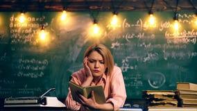 Una mujer lee un libro en una clase de escuela Aprendizaje de concepto Alumnos en uniforme Profesor en sala de clase metrajes