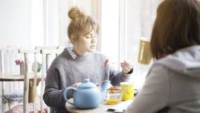 Una mujer linda joven que come la ensalada en un café imagenes de archivo