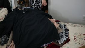 Una mujer llena para arriba la ropa en su cama que ella desea donar a la caridad almacen de metraje de vídeo