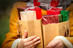 Una mujer lleva a cabo muchos regalos de Navidad Fotografía de archivo libre de regalías