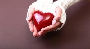 Una mujer lleva a cabo un corazón rojo en sus manos Foto de archivo