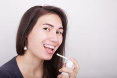 Una mujer lleva a cabo un espray para la medicina de la garganta foto de archivo libre de regalías