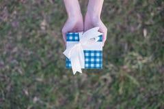 Una mujer lleva a cabo un giftbox azul con las manos en un fondo del césped fotografía de archivo