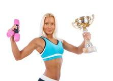 Una mujer lleva a cabo un par de pesas de gimnasia y de una taza de campeón fotografía de archivo