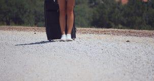 Una mujer lleva una maleta en el camino del guijarro metrajes