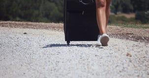 Una mujer lleva una maleta en el camino del guijarro almacen de video