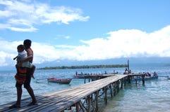 Una mujer lleva a su niño a la orilla Imágenes de archivo libres de regalías