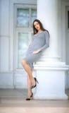 Una mujer lujosa en vestido gris claro cerca de una columna blanca La muchacha confiada está presentando al aire libre La señora  imágenes de archivo libres de regalías