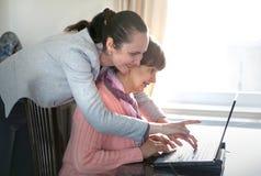Una mujer más joven que ayuda a una persona mayor que usa el ordenador portátil Imágenes de archivo libres de regalías