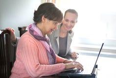 Una mujer más joven que ayuda a una persona mayor que usa el ordenador portátil Fotos de archivo libres de regalías