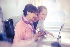 Una mujer más joven que ayuda a una persona mayor que usa el ordenador portátil Foto de archivo