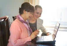 Una mujer más joven que ayuda a una persona mayor que usa el ordenador portátil para la búsqueda de Internet Fotos de archivo