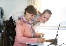 Una mujer más joven que ayuda a una persona mayor que usa el ordenador portátil para la búsqueda de Internet Imagen de archivo