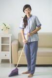 Una mujer más limpia de la criada con barrido Foto de archivo libre de regalías