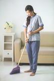 Una mujer más limpia de la criada con barrido Fotos de archivo libres de regalías