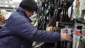Una mujer madura elige un sartén del arrabio en el supermercado