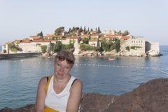 Una mujer madura en el fondo de la isla de Sveti Stefan Imágenes de archivo libres de regalías