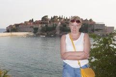 Una mujer madura en el fondo de la isla de Sveti Stefan Imagen de archivo