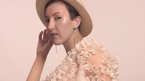 Una mujer marroquí joven lleva un sombrero en el estudio y el maquillaje monocromático almacen de metraje de vídeo