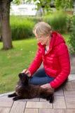 Una mujer mayor agradable frota ligeramente su gato apasionado Imagen de archivo libre de regalías