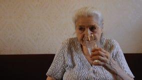 Una mujer mayor bebe el agua ` S de la abuela en sus meds almacen de metraje de vídeo