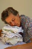 Una mujer mayor cayó en dormido en una pila de paños planchados Imagenes de archivo