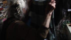 Una mujer mayor con clases grises del pelo con viejas cosas, limpia la cama en su casa vieja, viviendo solamente almacen de metraje de vídeo