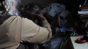 Una mujer mayor con clases grises del pelo con viejas cosas, limpia la cama en su casa vieja, viviendo solamente metrajes