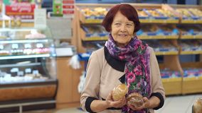 Una mujer mayor con las arrugas en su cara elige productos en el supermercado almacen de metraje de vídeo