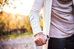 Una mujer mayor con una muleta en un paseo en naturaleza del otoño Foto de archivo libre de regalías
