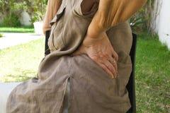 Una mujer mayor con un dolor de espalda que se sienta en la silla Imagen de archivo