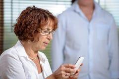 Una mujer mayor con un teléfono Fotos de archivo