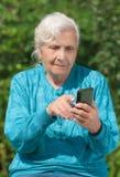 Una mujer mayor con un teléfono móvil Fotos de archivo
