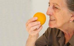 Una mujer mayor con una naranja Fotografía de archivo